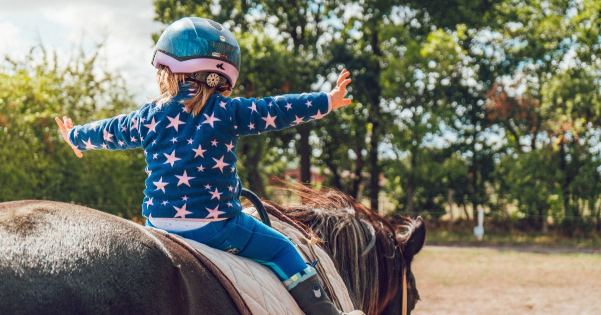 Small girl riding a horse, arms outstretched