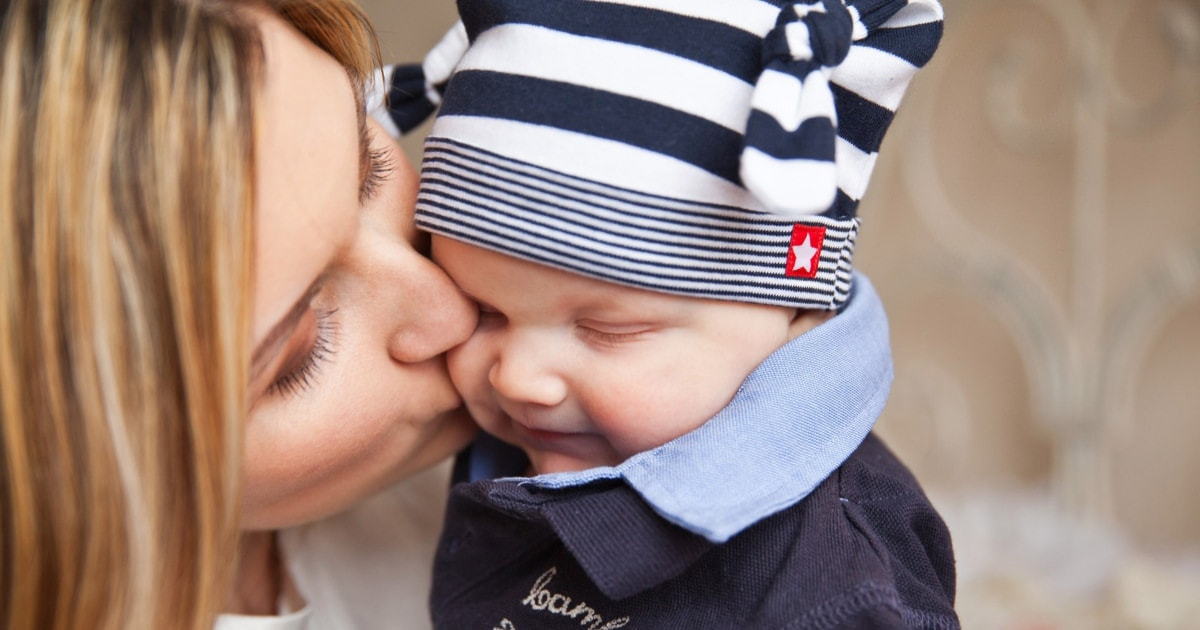 blonde mom kissing baby in blue and white striped hat