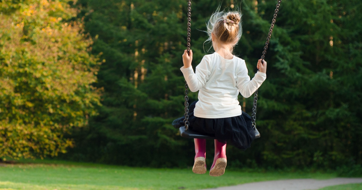 little girl swinging alone