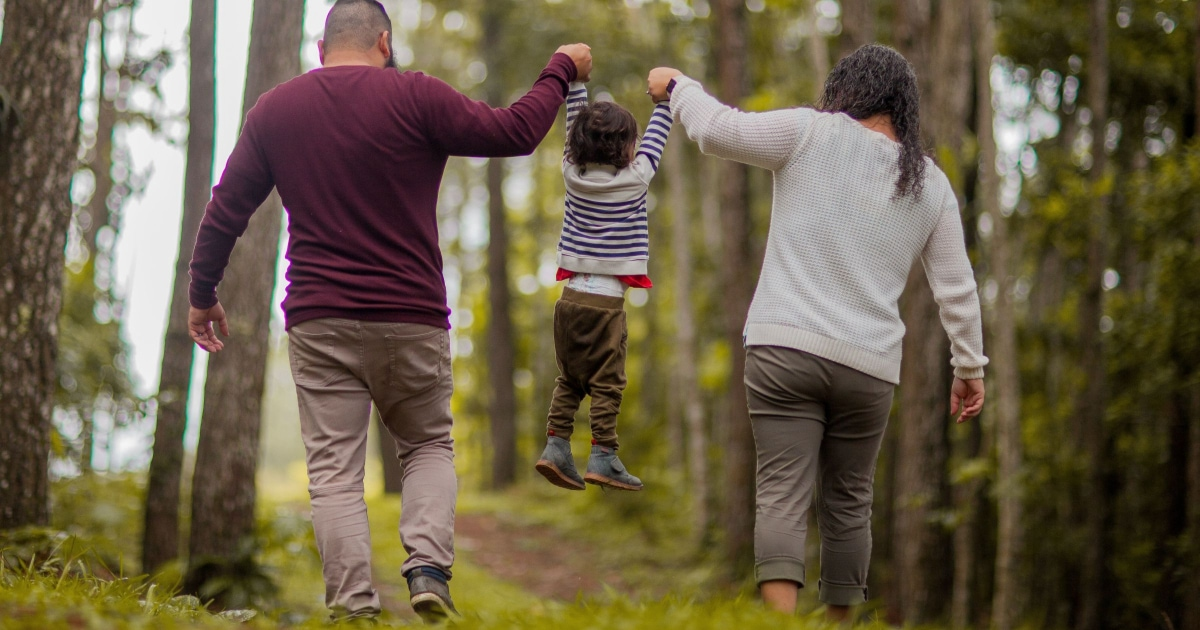 parents walking in woods, lifting toddler up between them