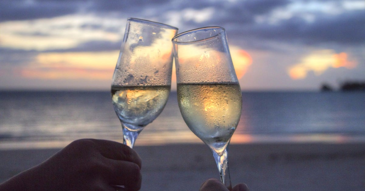Date nights for working moms can be absolutely essential for maintaining your sanity and your relationship! Pictured: two glasses clinking on a date night for working parents.
