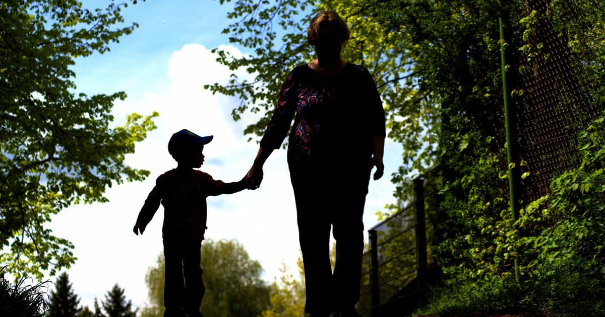 woman walking in shadow holding little boy's hand
