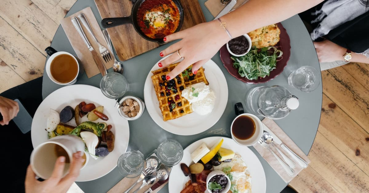 stock photo of aerial view of brunch table with hands reaching for waffles and coffee