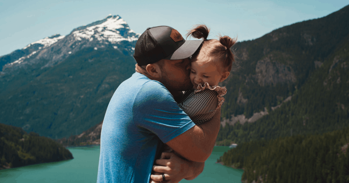 dad kissing pigtailed daughter in front of mountain range