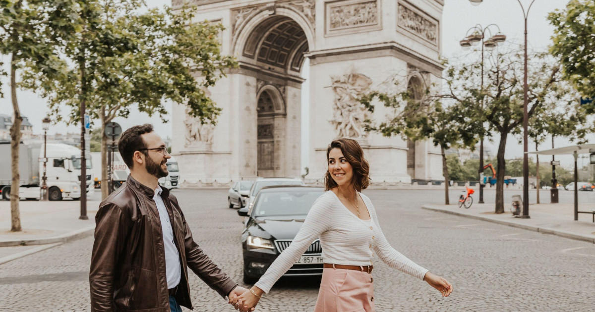 photo of man and woman walking in front of Paris landmark