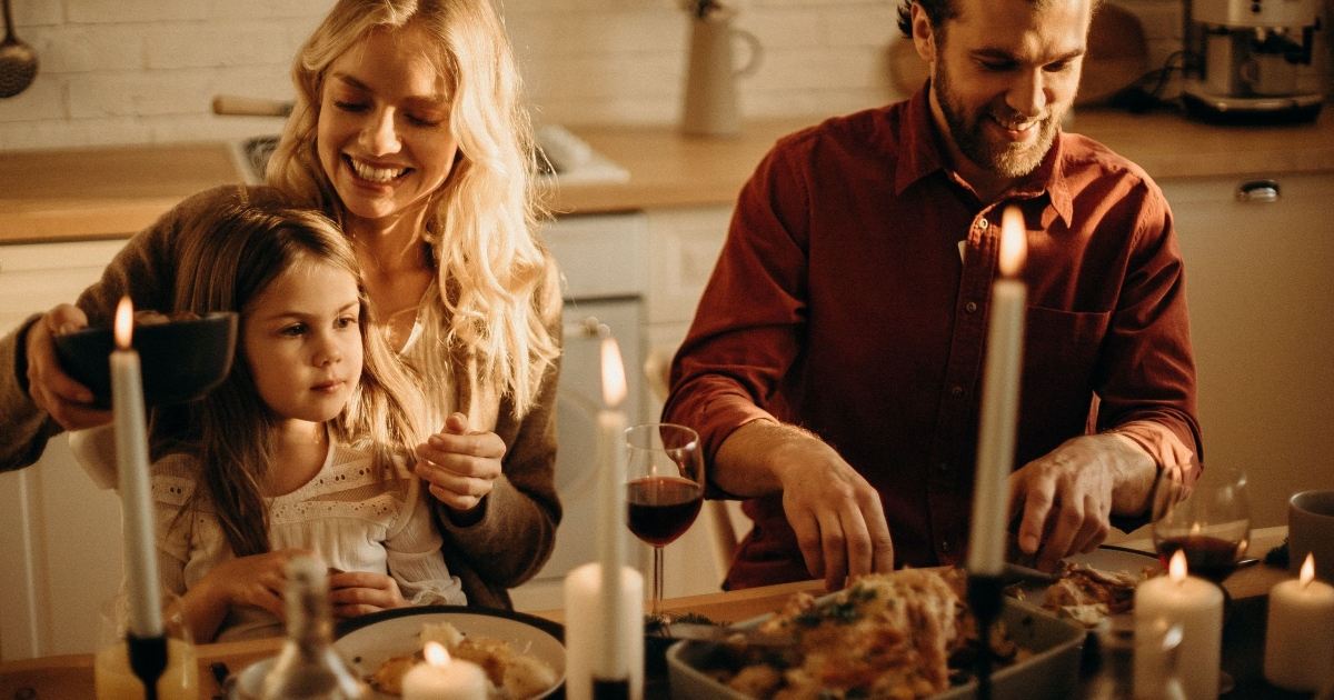 laughing couple at candlelit dinner with daughter on lap