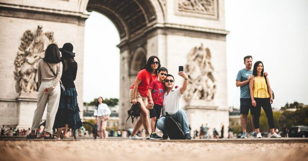 family with mom, son and father take photo in front of Parisian landmark, I think the Arc de Triomphe