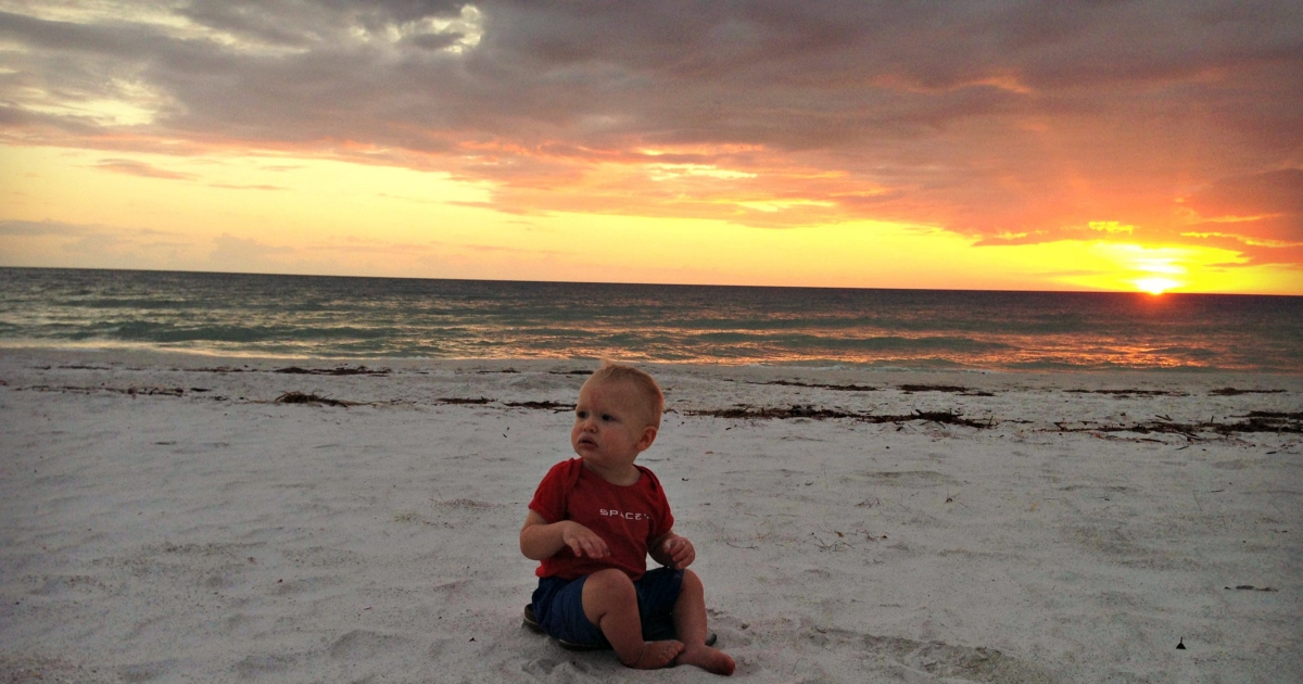 baby on beach at sunset