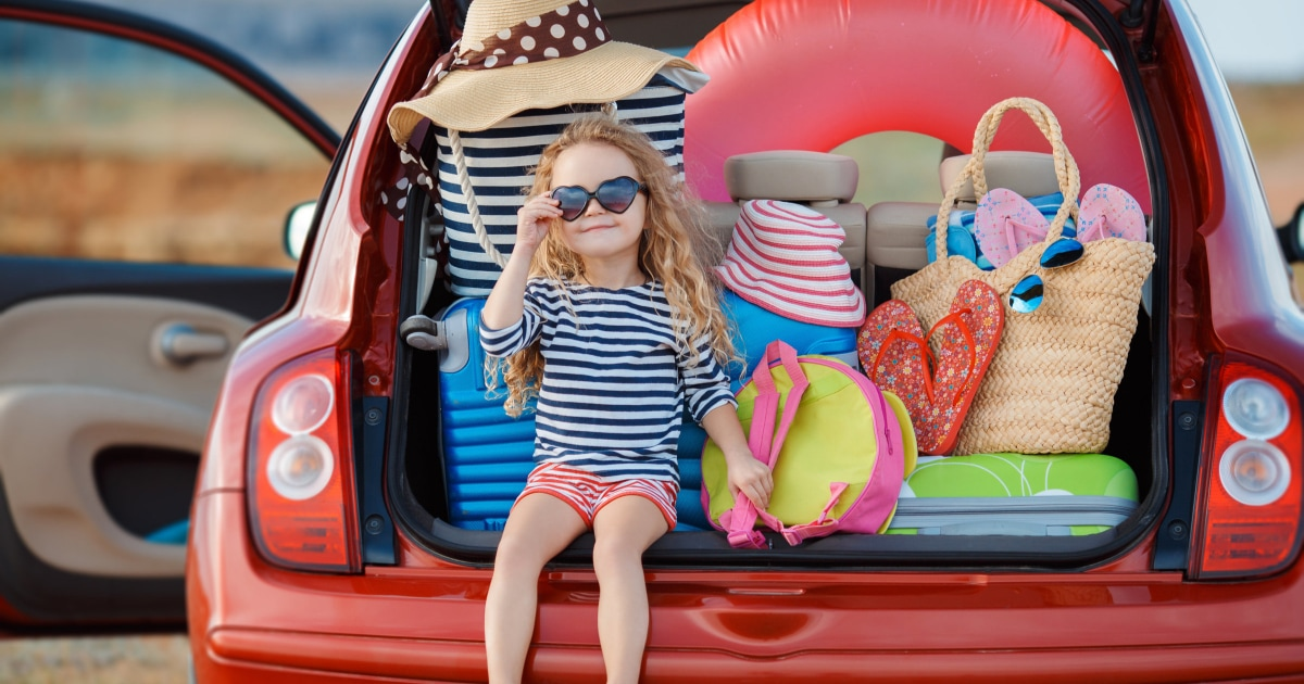 little girl sitting in open trunk with tons of beach gear inside