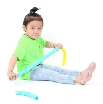 child playing with sensory pop tube