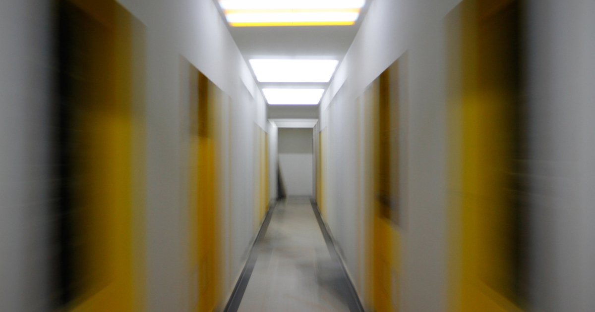 white hallway with yellow doors, photograph is blurred as if you're in motion