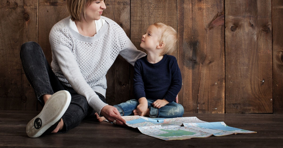 young professional mom making a silly face at her blond toddler son while they look at a map