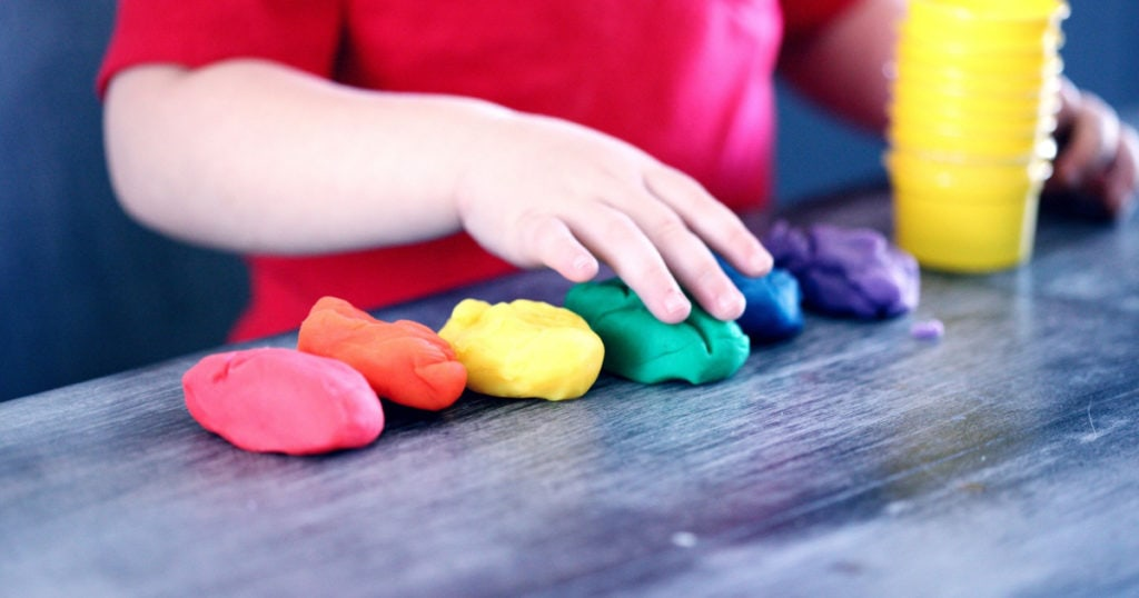 child playing with colorful playdoh