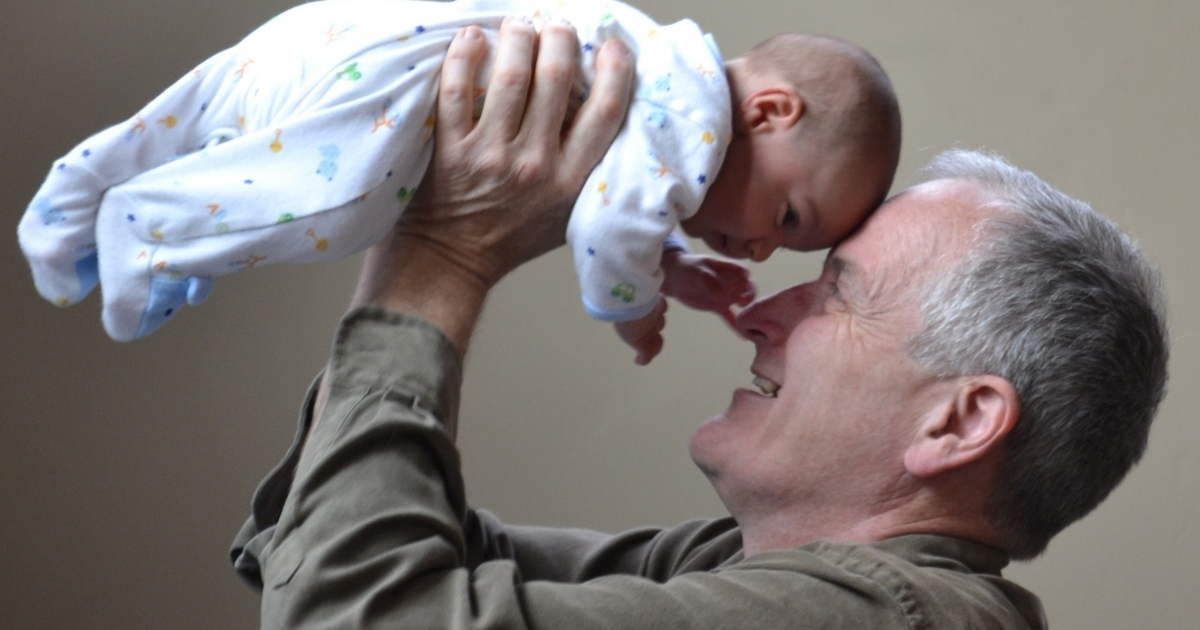 grandfather smiles at young baby