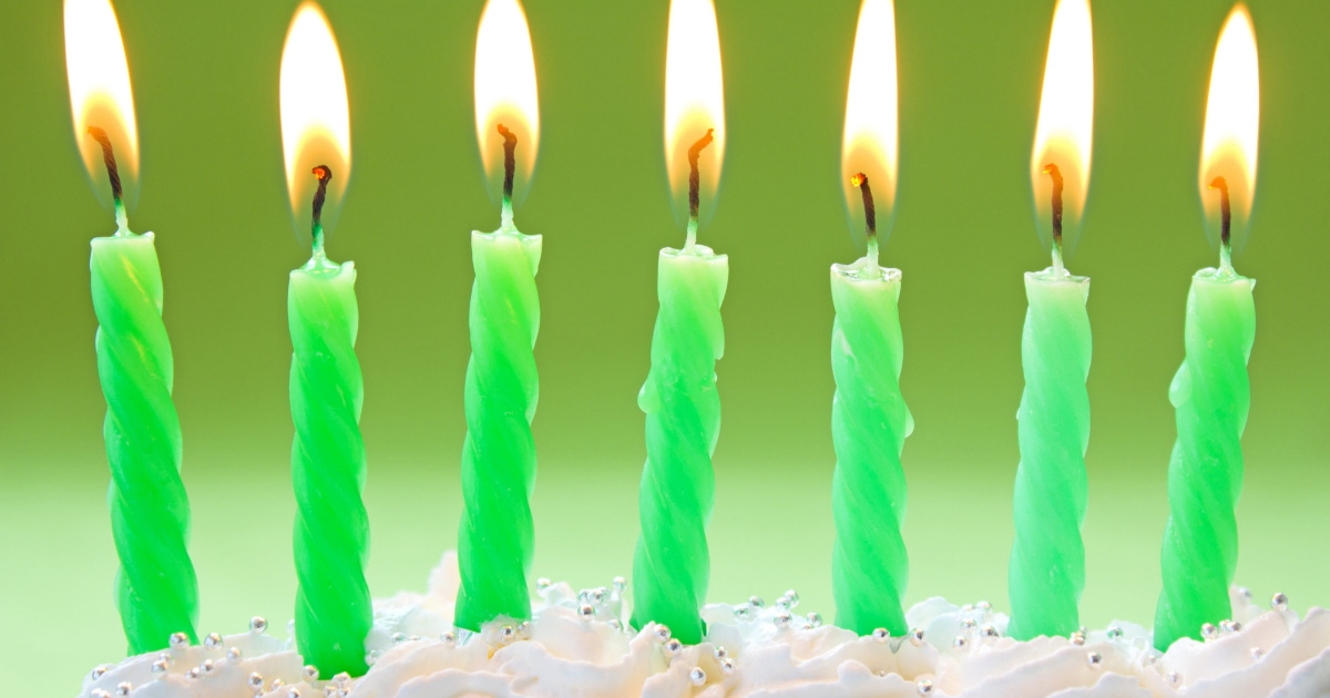 seven green, lit candles on top of a fluffy white cake
