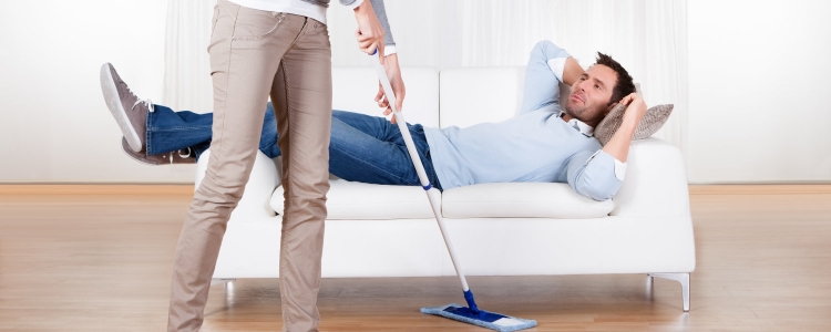 woman vacuuming while husband lounges on couch