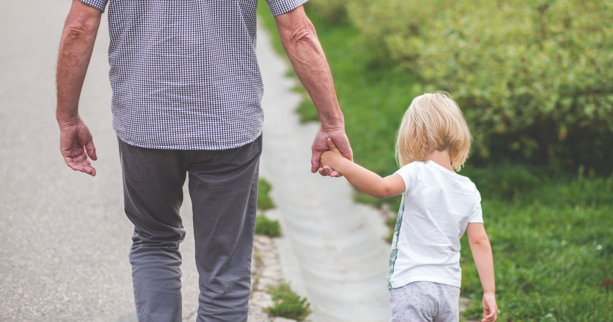 young blonde child with longish hair holding the hand of an older man and walking away from the camera