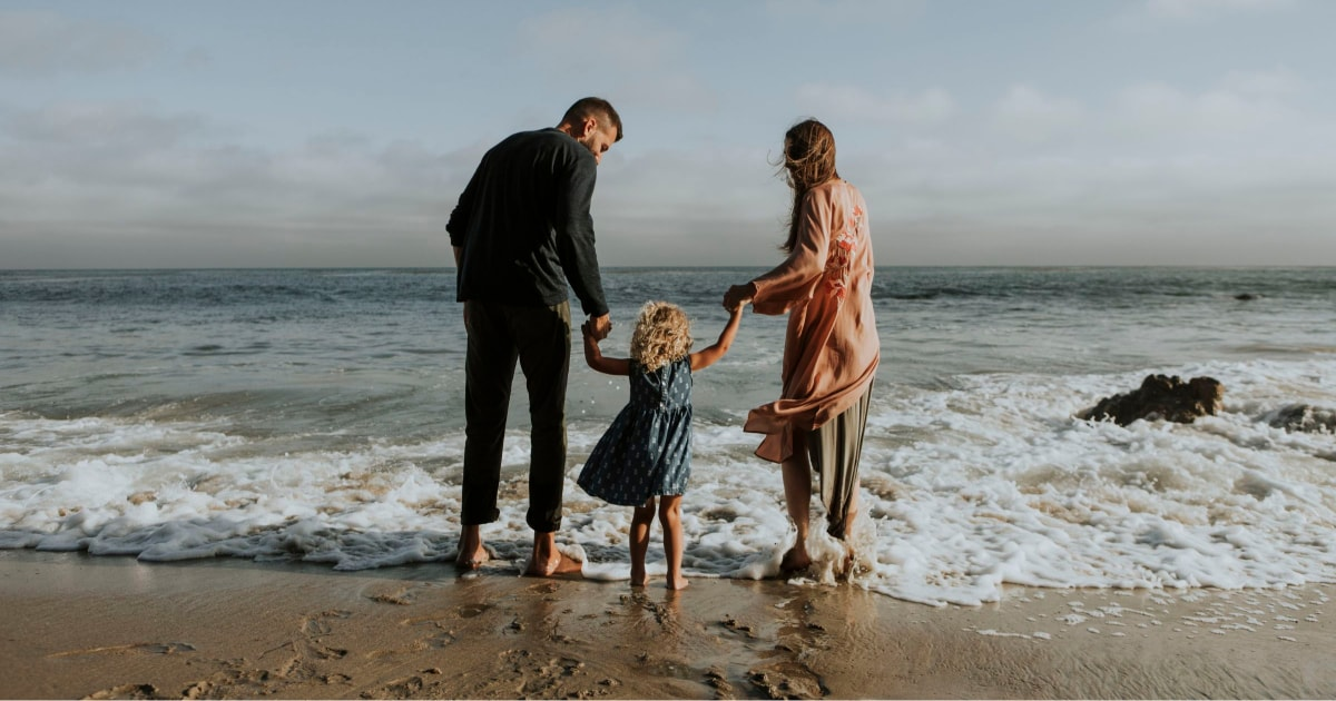 picture of a man and woman holding a little girl's hands as they walk into the surf