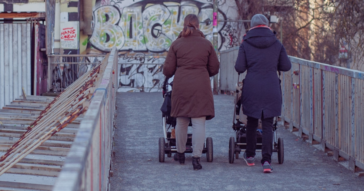 two women walking with strollers in an urban environment